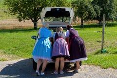 Tres muchachas en el Dirndl que mira en un coche-cargador del programa inicial Fotos de archivo libres de regalías