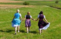 Tres muchachas en el Dirndl que se divierte Foto de archivo