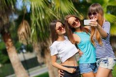 Tres muchachas en el fondo de palmeras Imagen de archivo