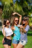 Tres muchachas en el fondo de palmeras Fotografía de archivo