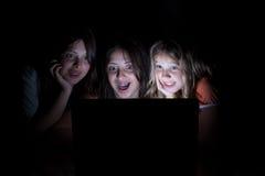 Tres muchachas en el ordenador en la noche Fotos de archivo