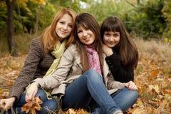 Tres muchachas en el parque del otoño. Fotografía de archivo