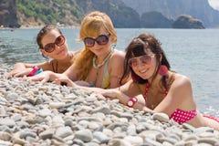 Tres muchachas en la costa Fotografía de archivo libre de regalías