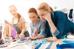 Tres muchachas en la fábrica de la ropa Están eligiendo los colores para el nuevo vestido imagen de archivo