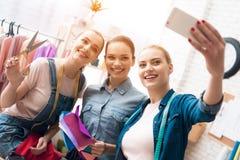 Tres muchachas en la fábrica de la ropa Están tomando el selfie desining el nuevo vestido fotos de archivo libres de regalías