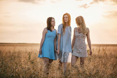 Tres muchachas en la puesta del sol Imagenes de archivo