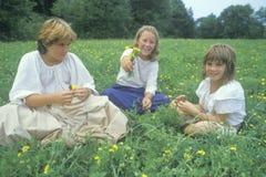 Tres muchachas en un prado de flores amarillas, granja, PA Fotos de archivo libres de regalías