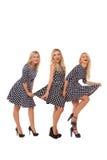 Tres muchachas en vestidos del punto y zapatos negros Foto de archivo