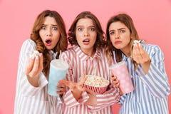 Tres muchachas fascinadoras en homewear que comen palomitas de maíz y la consumición Imagenes de archivo