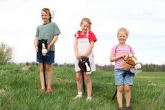 Tres muchachas felices con los caballos de palillo. Fotos de archivo libres de regalías