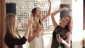 Tres muchachas felices con vidrios de champán en las manos que bailan en restaurante almacen de metraje de vídeo