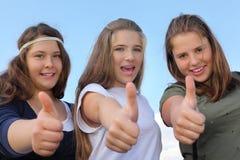 Tres muchachas felices manosean con los dedos para arriba en el fondo del cielo Imágenes de archivo libres de regalías
