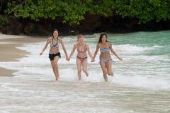 Tres muchachas funcionadas con en la playa foto de archivo