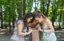 Tres muchachas hermosas abren el paquete con los anillos de espuma en parque Imagen de archivo libre de regalías