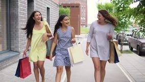 Tres muchachas hermosas caminan abajo de la calle después de hacer compras 4K almacen de metraje de vídeo