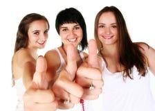 Tres muchachas hermosas con los pulgares para arriba Imagenes de archivo