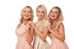 Tres muchachas hermosas en los vestidos de la moda aislados Foto de archivo