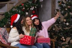 Tres muchachas hermosas en sonrisas de los sombreros de santa hacen selfies cerca de Fotos de archivo libres de regalías