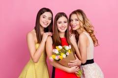 Tres muchachas hermosas felices junto en vestidos elegantes con hai Foto de archivo