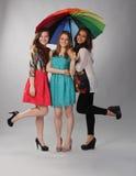 Tres muchachas hermosas que actúan para arriba debajo de un paraguas Imagen de archivo libre de regalías