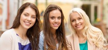 Tres muchachas hermosas que beben el café en café Imagenes de archivo