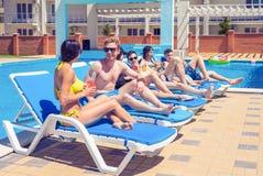 Tres muchachas hermosas que beben los cócteles cerca de la piscina Imagen de archivo libre de regalías