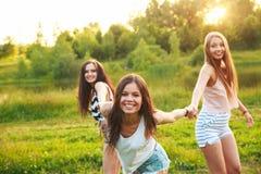 Tres muchachas hermosas que caminan y que ríen en puesta del sol en el parque Concepto de la amistad Imagen de archivo libre de regalías