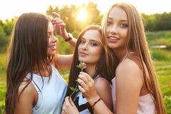 Tres muchachas hermosas que caminan y que ríen en puesta del sol en el parque Concepto de la amistad Imagenes de archivo