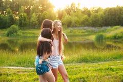 Tres muchachas hermosas que caminan y que ríen en puesta del sol en el parque Concepto de la amistad Fotos de archivo