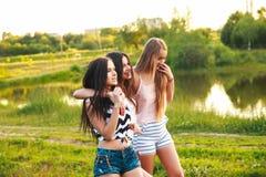 Tres muchachas hermosas que caminan y que ríen en puesta del sol en el parque Concepto de la amistad Fotos de archivo libres de regalías