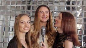 Tres muchachas hermosas que cantan en micrófono en la barra del Karaoke almacen de metraje de vídeo