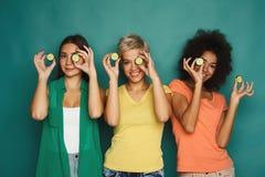 Tres muchachas hermosas que cubren ojos con los pedazos del pepino Fotos de archivo