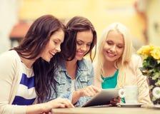 Tres muchachas hermosas que miran la PC de la tableta en café Foto de archivo libre de regalías