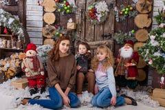 Tres muchachas hermosas que presentan en decoraciones de la Navidad Imágenes de archivo libres de regalías