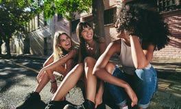 Tres muchachas hermosas que se sientan al aire libre por el camino Imagen de archivo libre de regalías