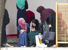 Tres muchachas islámicas se sientan en el patio del husrev de Gazi piden la mezquita Imagen de archivo