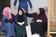 Tres muchachas islámicas se sientan en el patio del husrev de Gazi piden la mezquita Imagenes de archivo