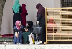 Tres muchachas islámicas se sientan en el patio del husrev de Gazi piden la mezquita Imagen de archivo libre de regalías
