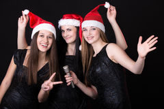 Tres muchachas jovenes atractivas de santa con el micrófono Fotos de archivo libres de regalías