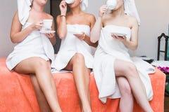 Tres muchachas lindas jovenes en las albornoces blancas est?n bebiendo t? en el sal?n del balneario Resto despu?s de procedimient fotografía de archivo libre de regalías