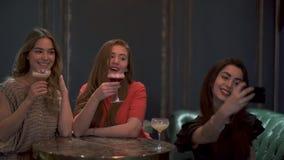 Tres muchachas lindas se sientan en un café o un restaurante que plantea y que toma maravillosamente un selfie de la foto para la almacen de metraje de vídeo