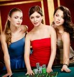 Tres muchachas ponen una apuesta que juega la ruleta Fotos de archivo libres de regalías