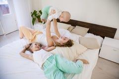 Tres muchachas por la mañana que miente en cama Foto de archivo libre de regalías