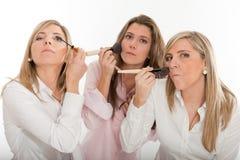 Tres muchachas que aplican maquillaje Fotografía de archivo libre de regalías