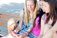 Tres muchachas que charlan con sus smartphones Fotografía de archivo