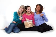 Tres muchachas que comen las palomitas imagenes de archivo