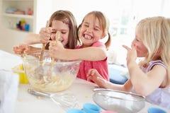 Tres muchachas que hacen las magdalenas en cocina Fotos de archivo libres de regalías