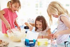Tres muchachas que hacen las magdalenas en cocina Imagen de archivo