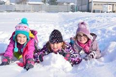Tres muchachas que juegan en la nieve Fotografía de archivo libre de regalías