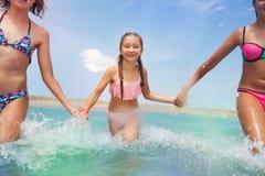 Tres muchachas que llevan a cabo las manos que corren en el mar Imagen de archivo libre de regalías